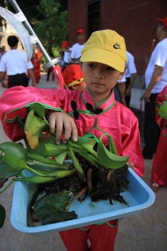 ▲青蛙由當地溪口小學女童捧著